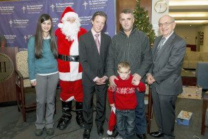 Valon Syla stands with his father, along with Santa Claus and St. Francis staff members
