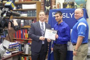 Roslyn's Athletic Director Peter Melore and Roslyn High School Principal Dr. Scott Andrews congratulate Sahil Anand.